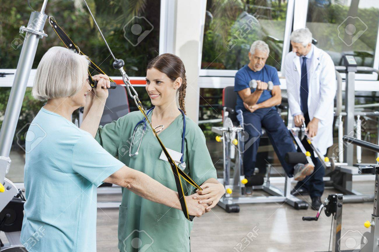 Happy female nurse assisting senior woman with resistance band exercise in rehab fitness center - 57364870