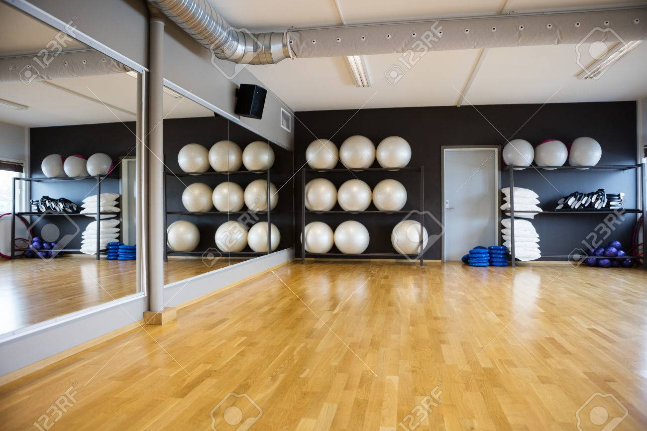 Pilate balls arranged in shelves by mirror at gym - 57364803