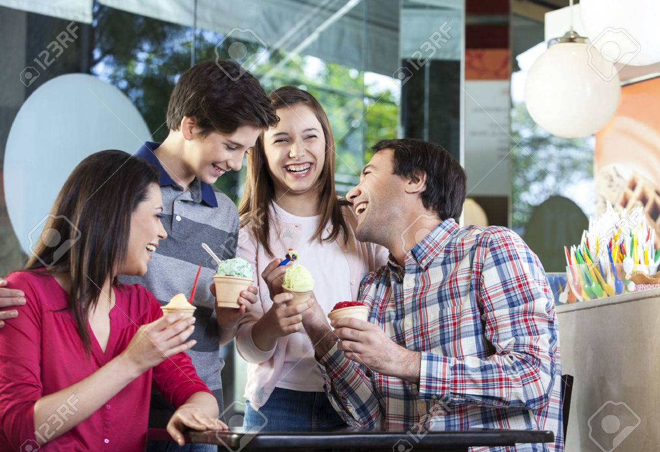 Family of four laughing while having ice creams at table in parlor - 59134201