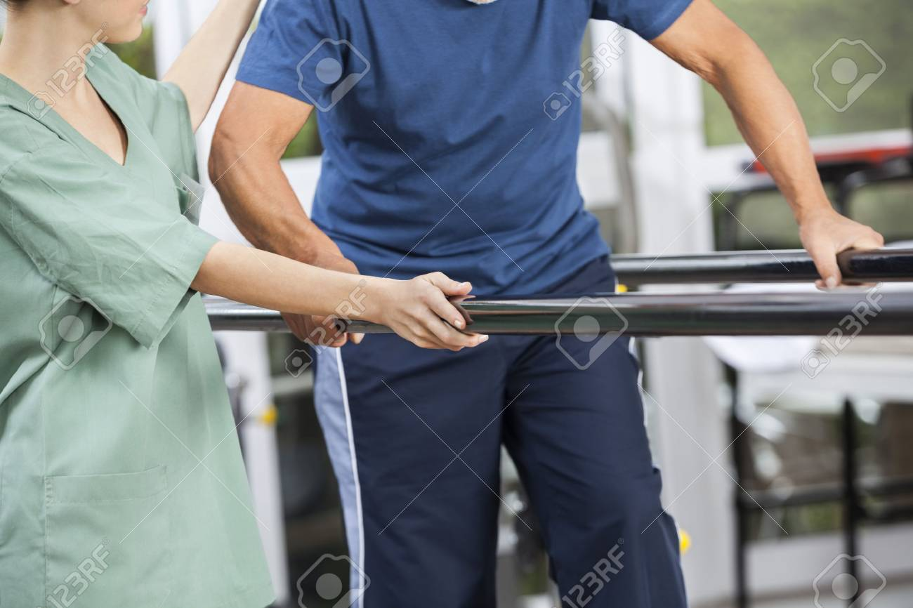Midsection of female physiotherapist standing by senior man walking between parallel bars in fitness center - 59134216