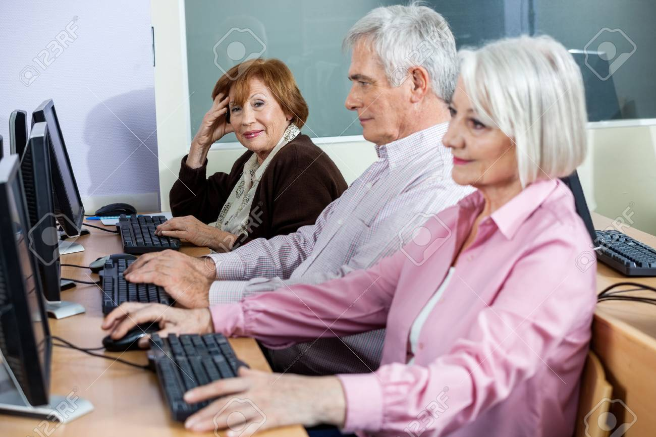 Portrait of smiling senior woman sitting in computer class with classmates studying at desk - 60169611