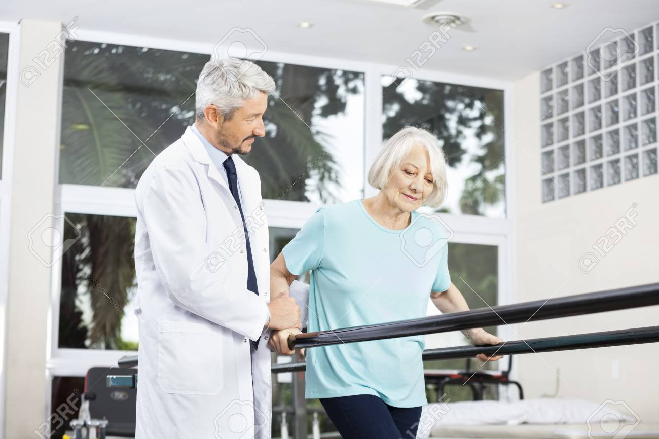 Mature male doctor looking at senior woman walking between parallel bars in fitness studio at rehab center - 59134264