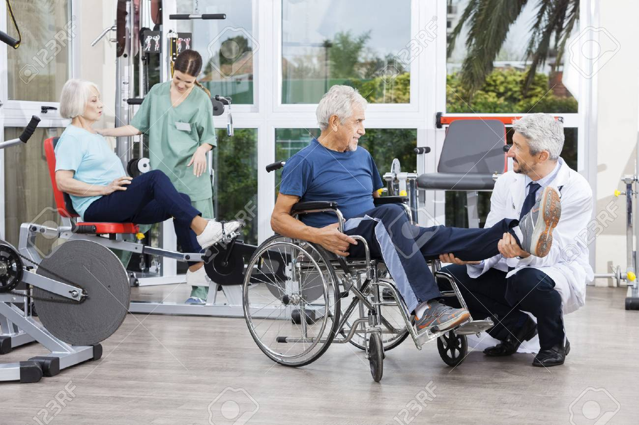 Male and female physiotherapists guiding patients to exercise at rehab fitness center - 58217211