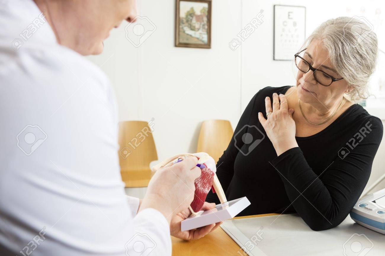 Male doctor explaining shoulder rotator cuff model to senior woman in clinic Standard-Bild - 58217214