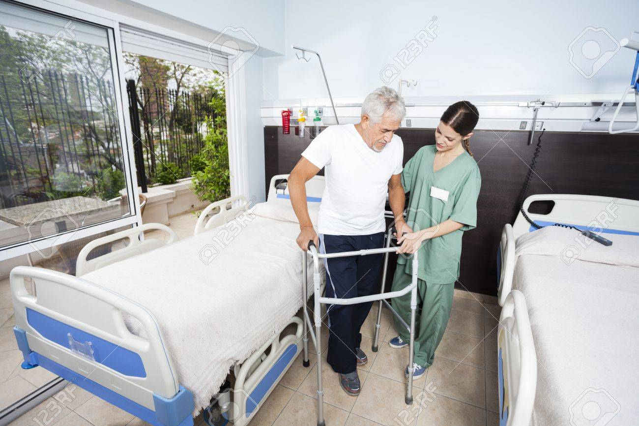 Female nurse helping senior male patient in using walker at rehab center - 58408428