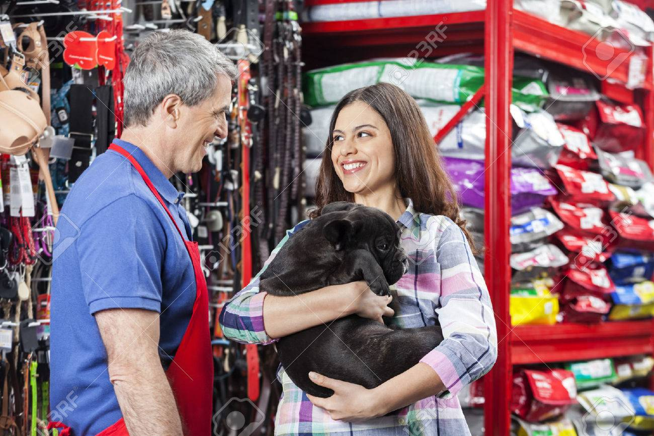Happy woman carrying French Bulldog while standing with salesman in pet store Standard-Bild - 60664327