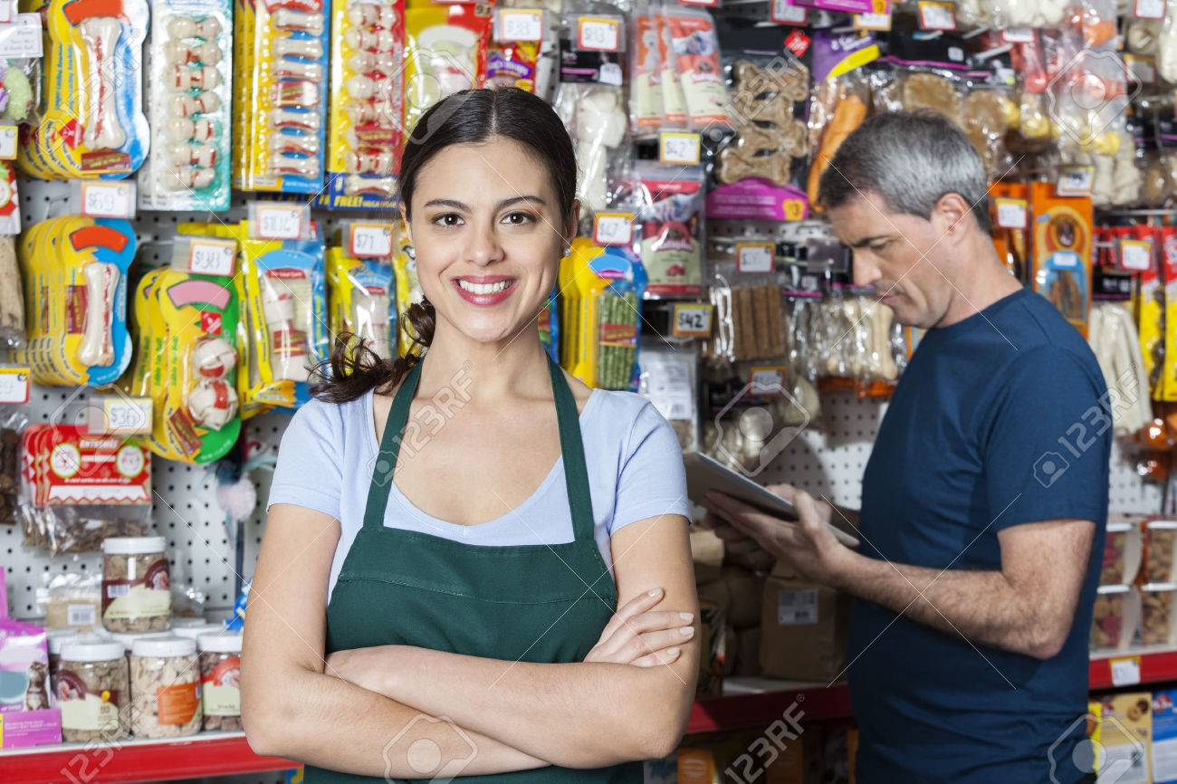 Portrait of confident saleswoman with arms crossed standing while customer selecting product in store - 58988042