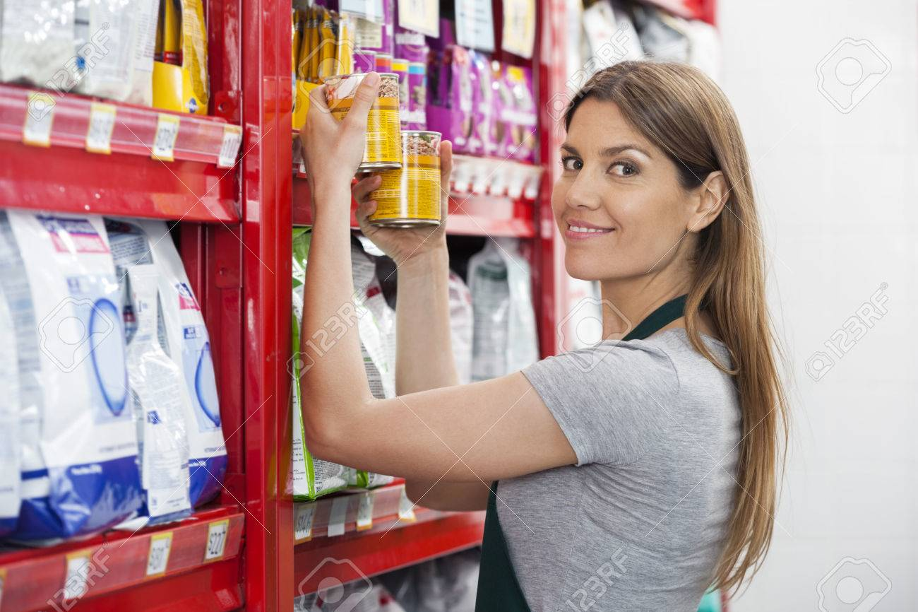 Portrait of confident saleswoman holding food cans by shelves in pet store - 58989371