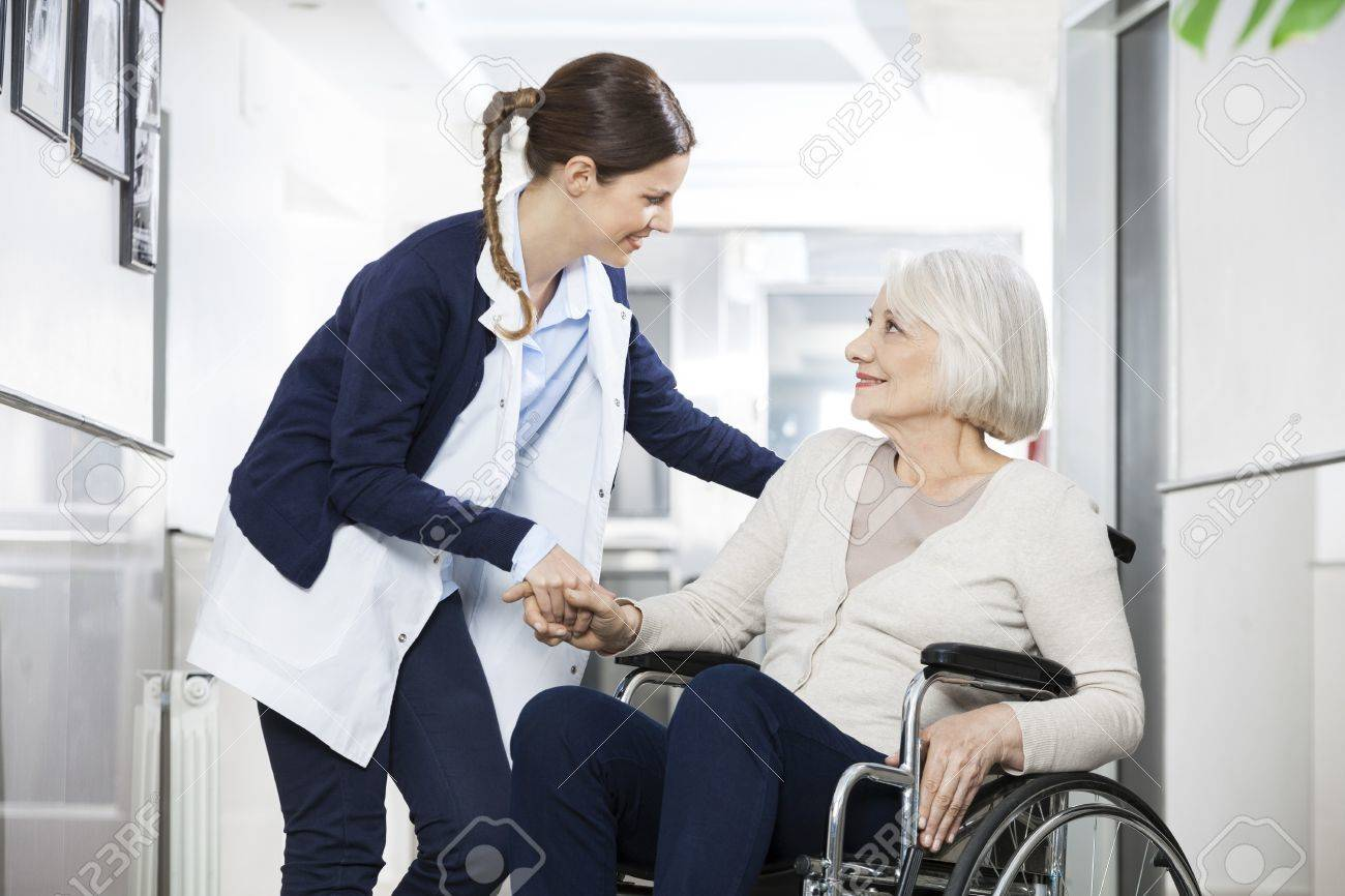 Friendly physiotherapist consoling senior woman sitting in wheelchair at rehab center - 59147049