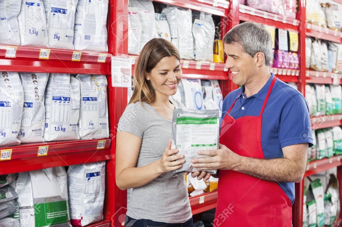 Mature salesman assisting female customer in buying pet food at shop - 59134328