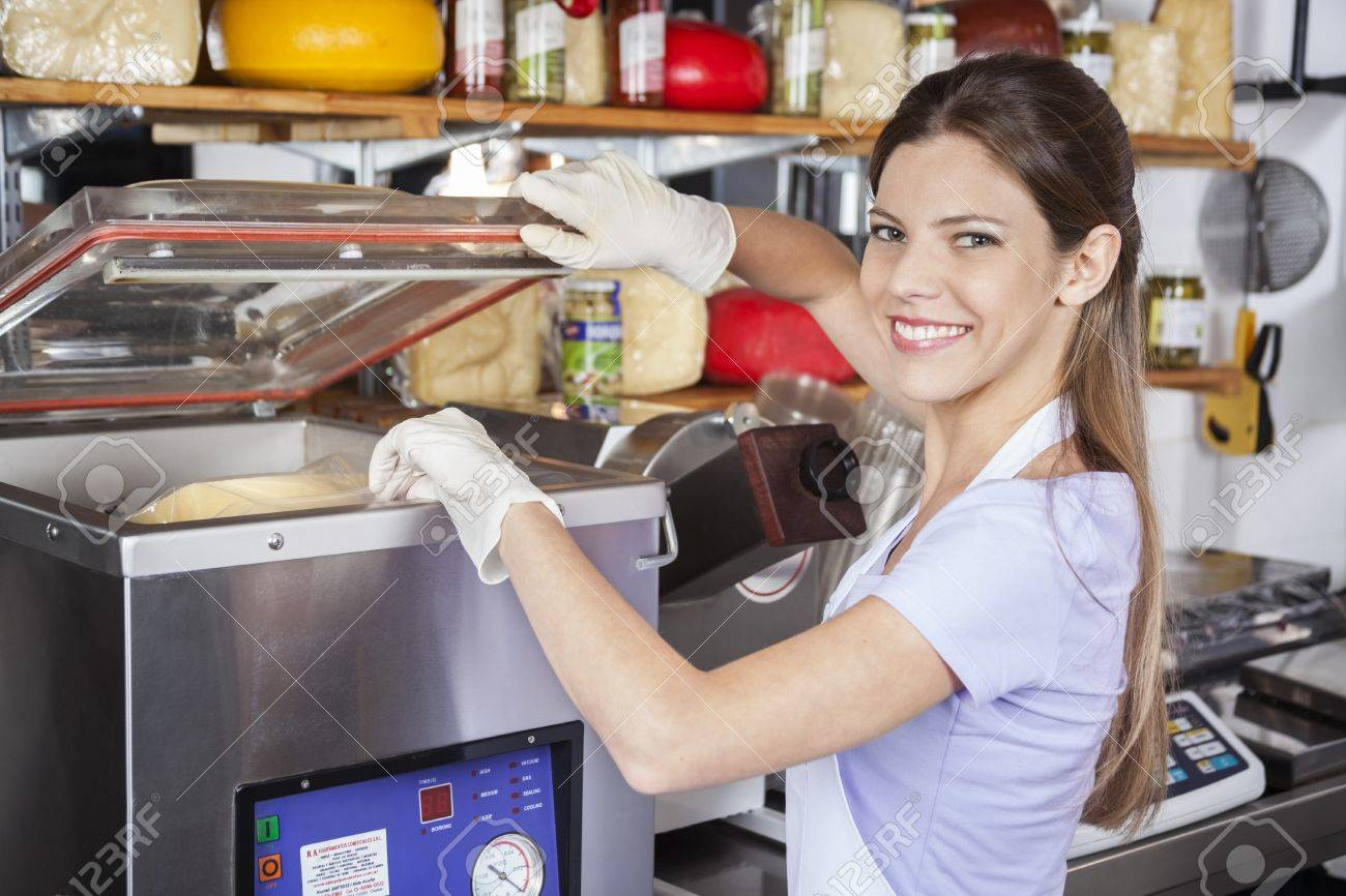 Portrait of smiling young saleswoman using vacuum packing machine in grocery store - 61223903