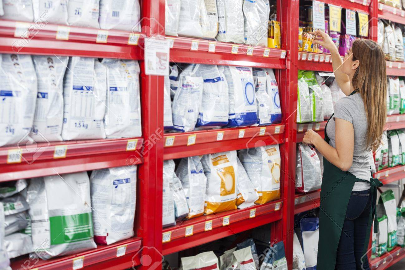 Side view of saleswoman arranging food packages on shelf in pet store - 61616731