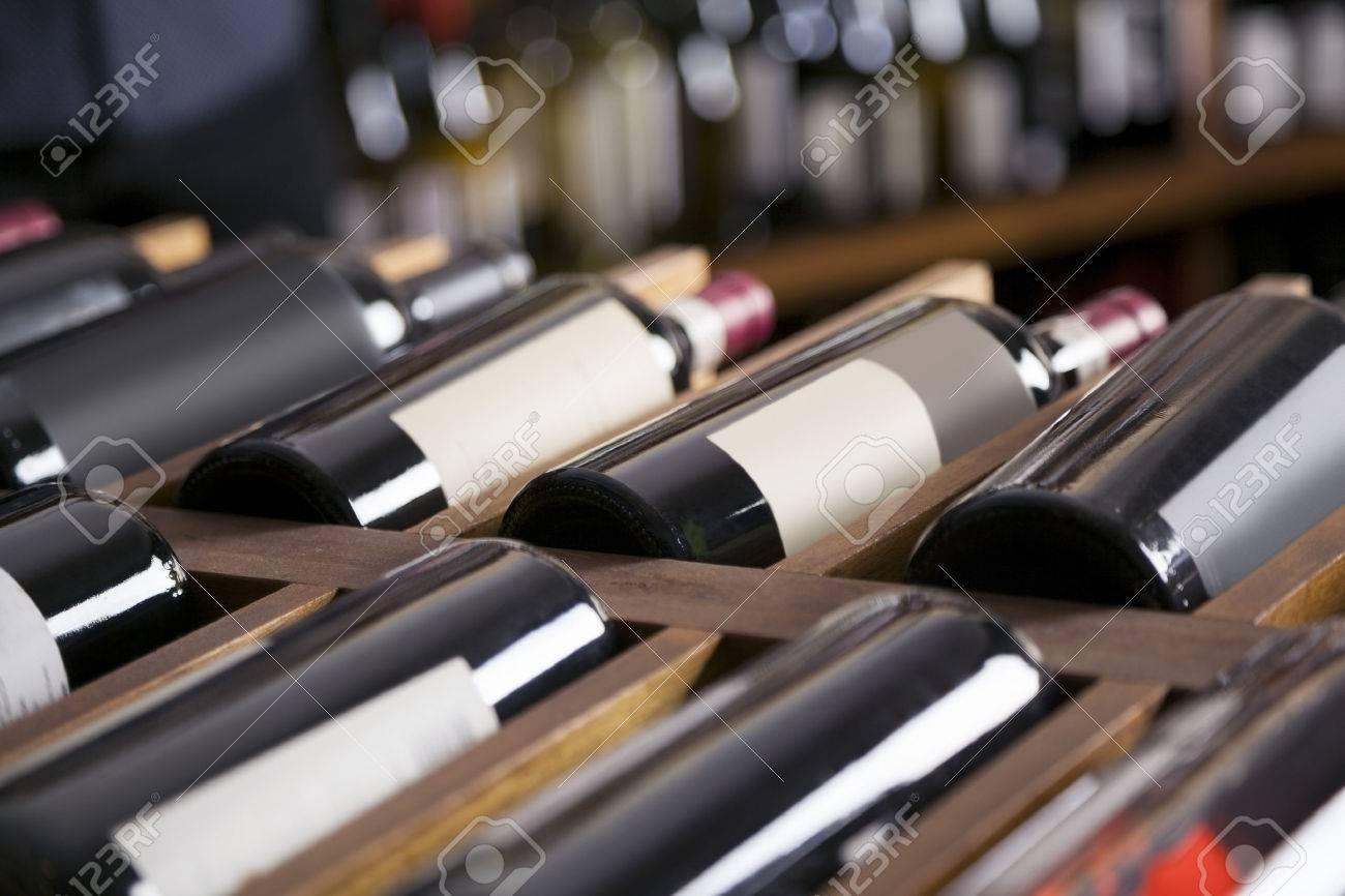 Red wine bottles displayed on shelves in supermarket - 65221903