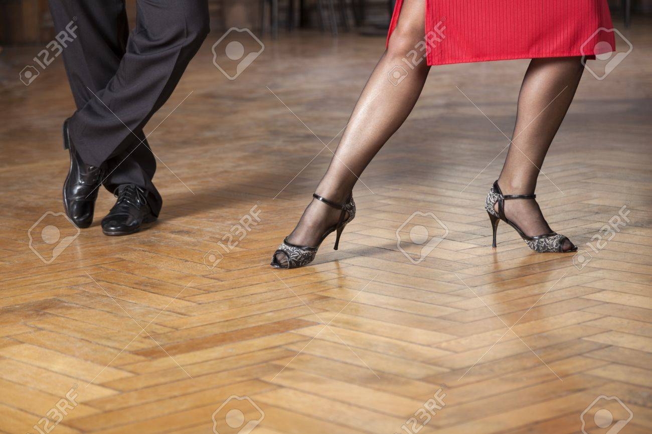 Low section of tango professionals performing on hardwood floor in cafe - 65222009