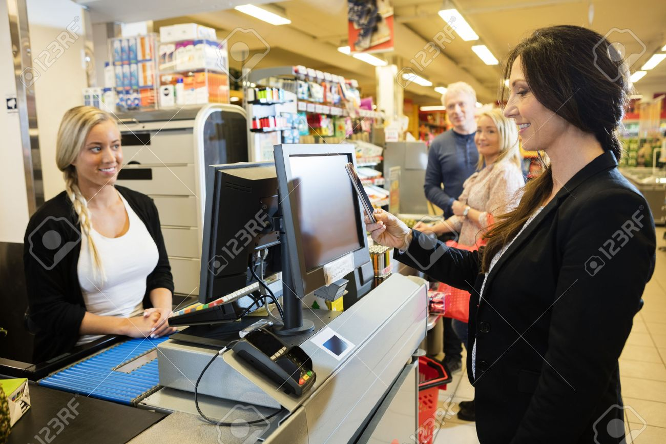 Smiling cashier looking at female customer making NFC payment at checkout counter in grocery store - 64972164