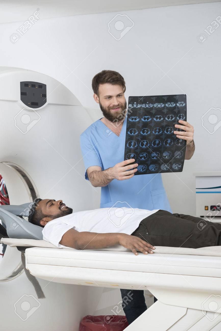 Radiologe, Der Röntgenstrahl-Bericht Hält, Während Patient Auf CT ...