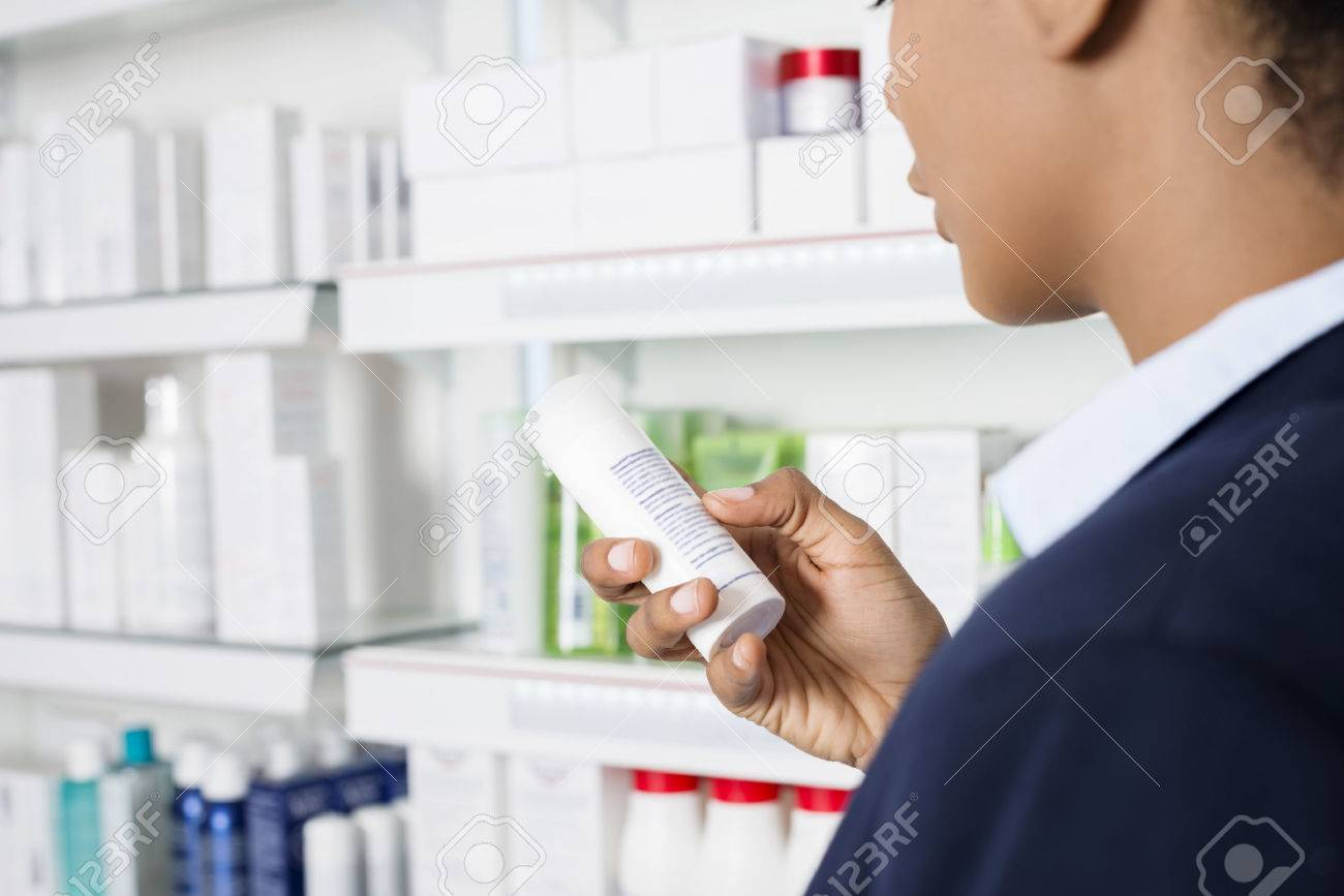 Businesswoman Reading Instructions Medicine Bottle At Pharmacy - 73128722