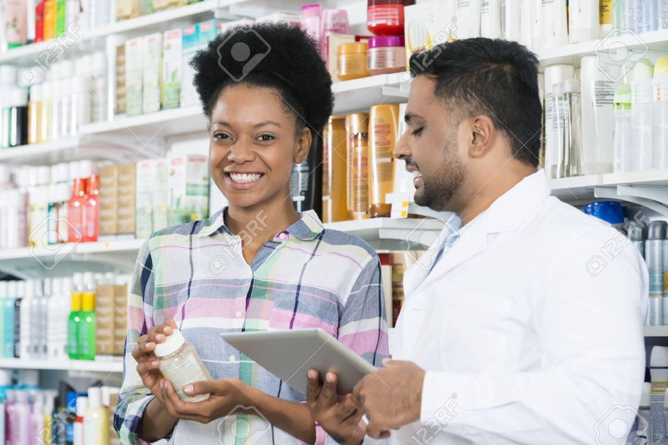 Customer Holding Product While Standing By Chemist - 74606519