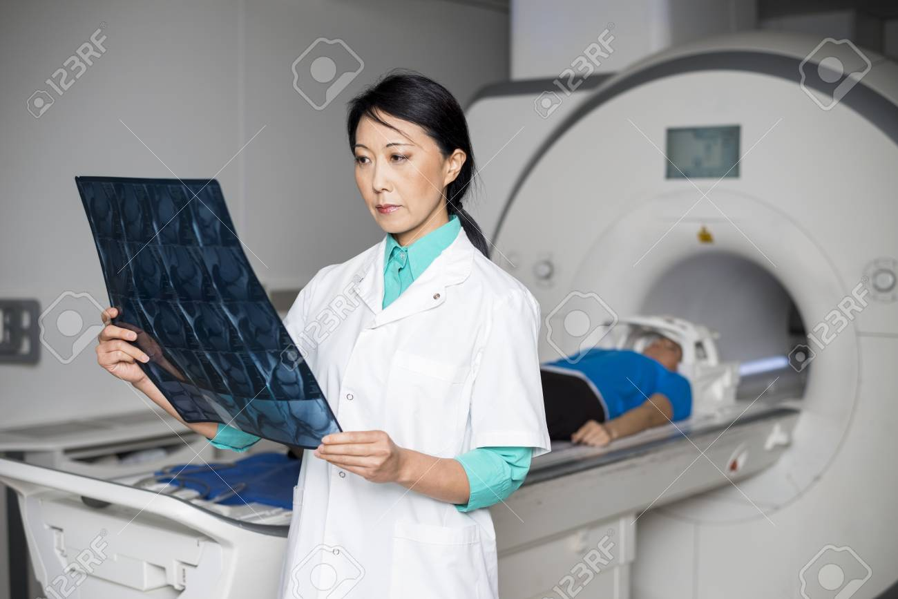 Doctor Analyzing X-ray While Patient Lying On CT Scan Machine - 74763691