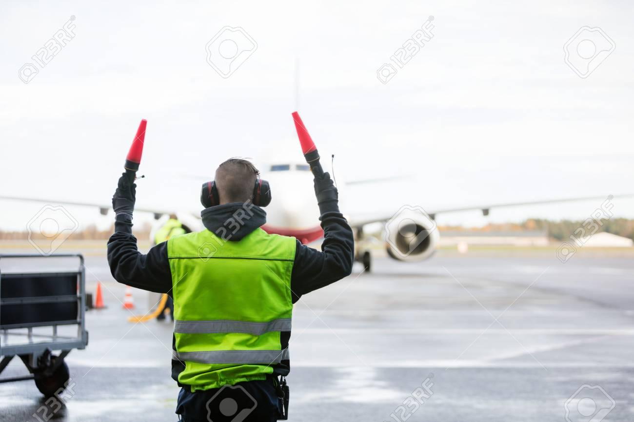 Ground Crew Signaling To Airplane - 86583200