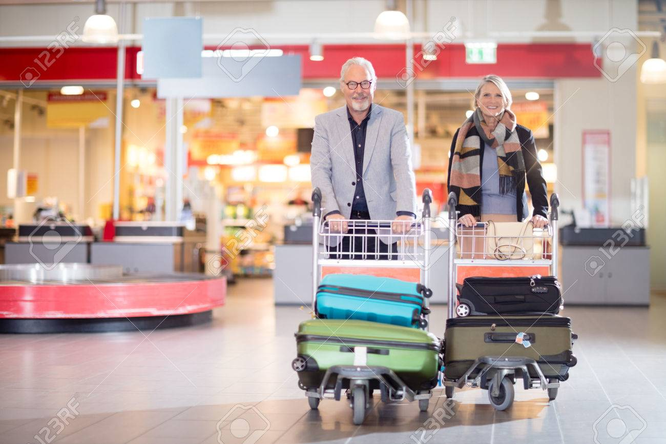 Happy Senior Business Couple With Luggage In Carts At Airport - 87016722