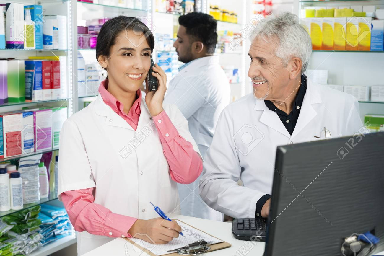 Chemist Looking At Female Colleague Using Telephone At Counter - 87595748