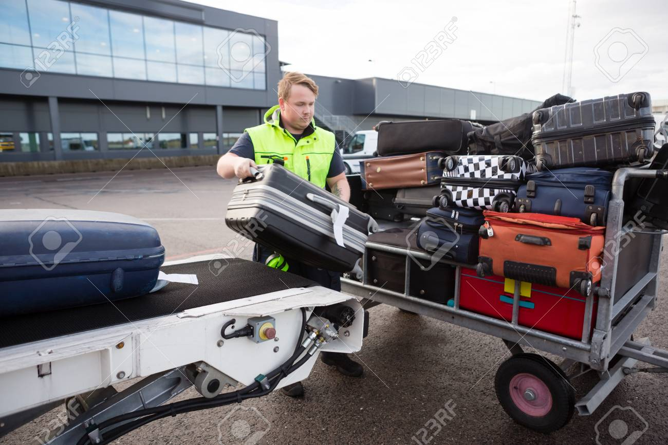 Worker Stacking Luggage On Trailer From Conveyor On Runway - 90465405