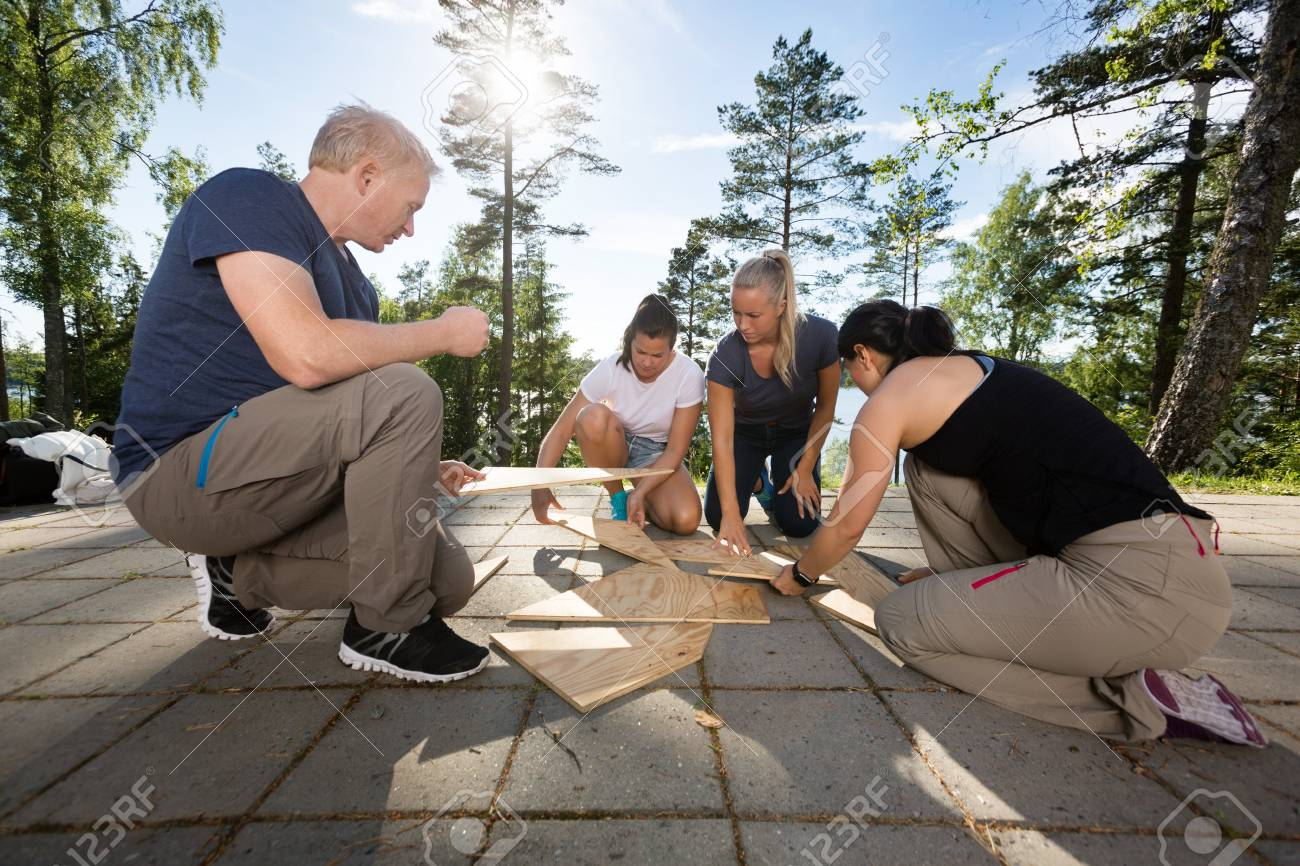 Coworkers Solving Wooden Plank Puzzle On Patio - 91041224