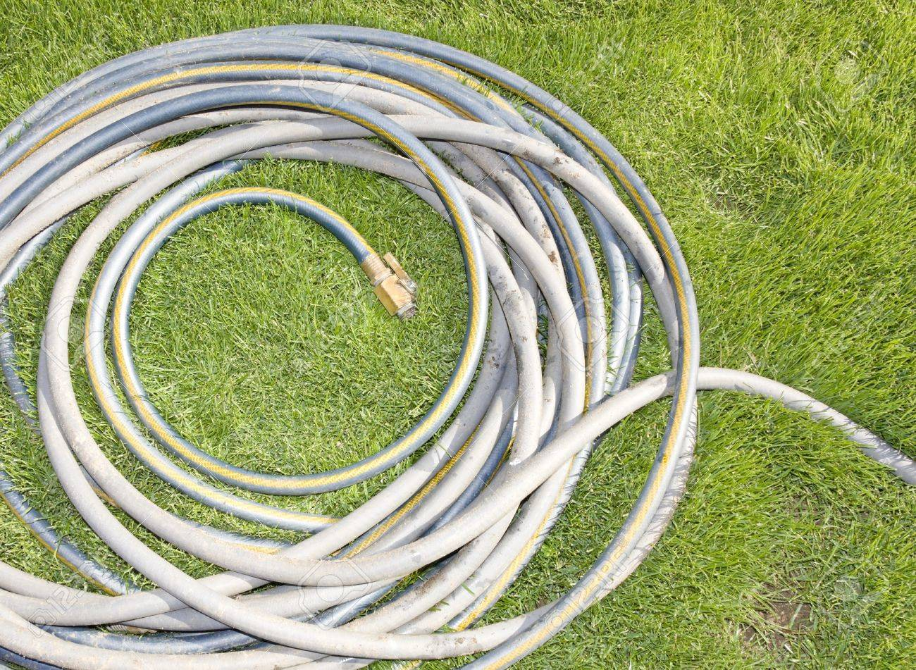 Coiled Garden Hose In The Grass Top View Of A Grey Rubber Water