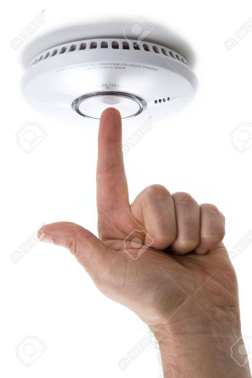 hand with pointing finger testing a domestic fire / smoke alarm detector  isolated on a white background Stock Photo - 11905797