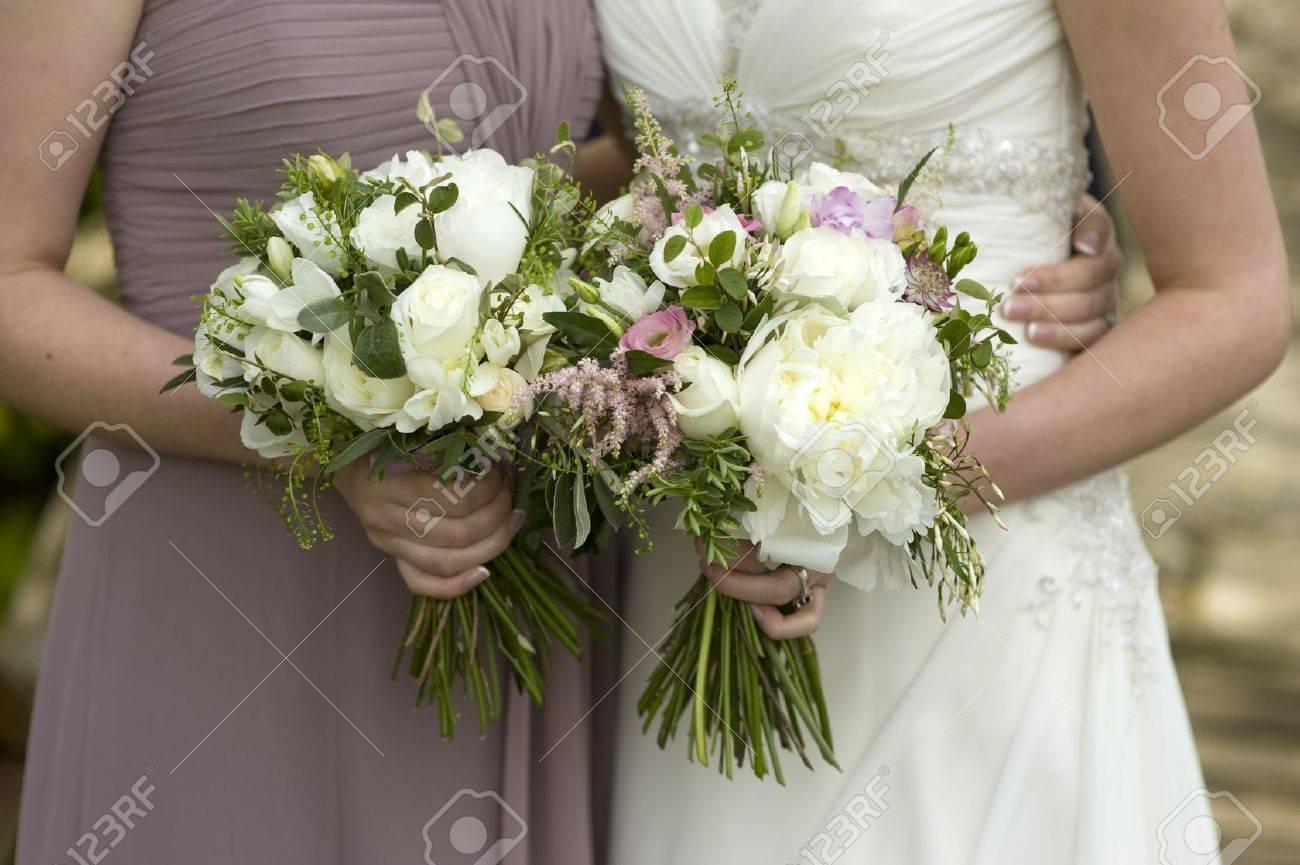 mariée et demoiselle d'honneur tenant des bouquets de mariage