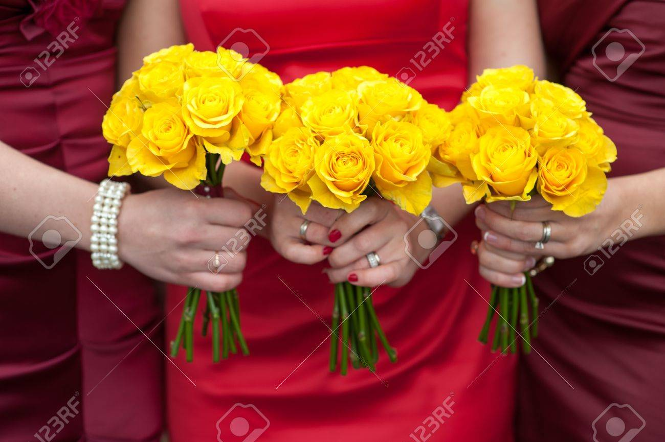 Three Bridesmaids Holding Wedding Bouquets Of Yellow Roses Stock