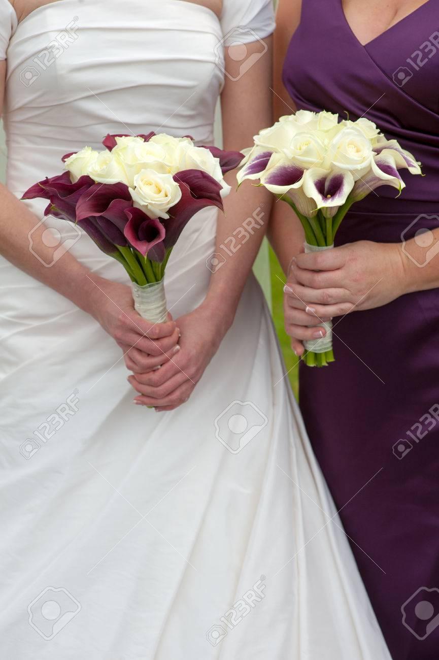 mariée et de demoiselle d'honneur tenant des bouquets de mariage