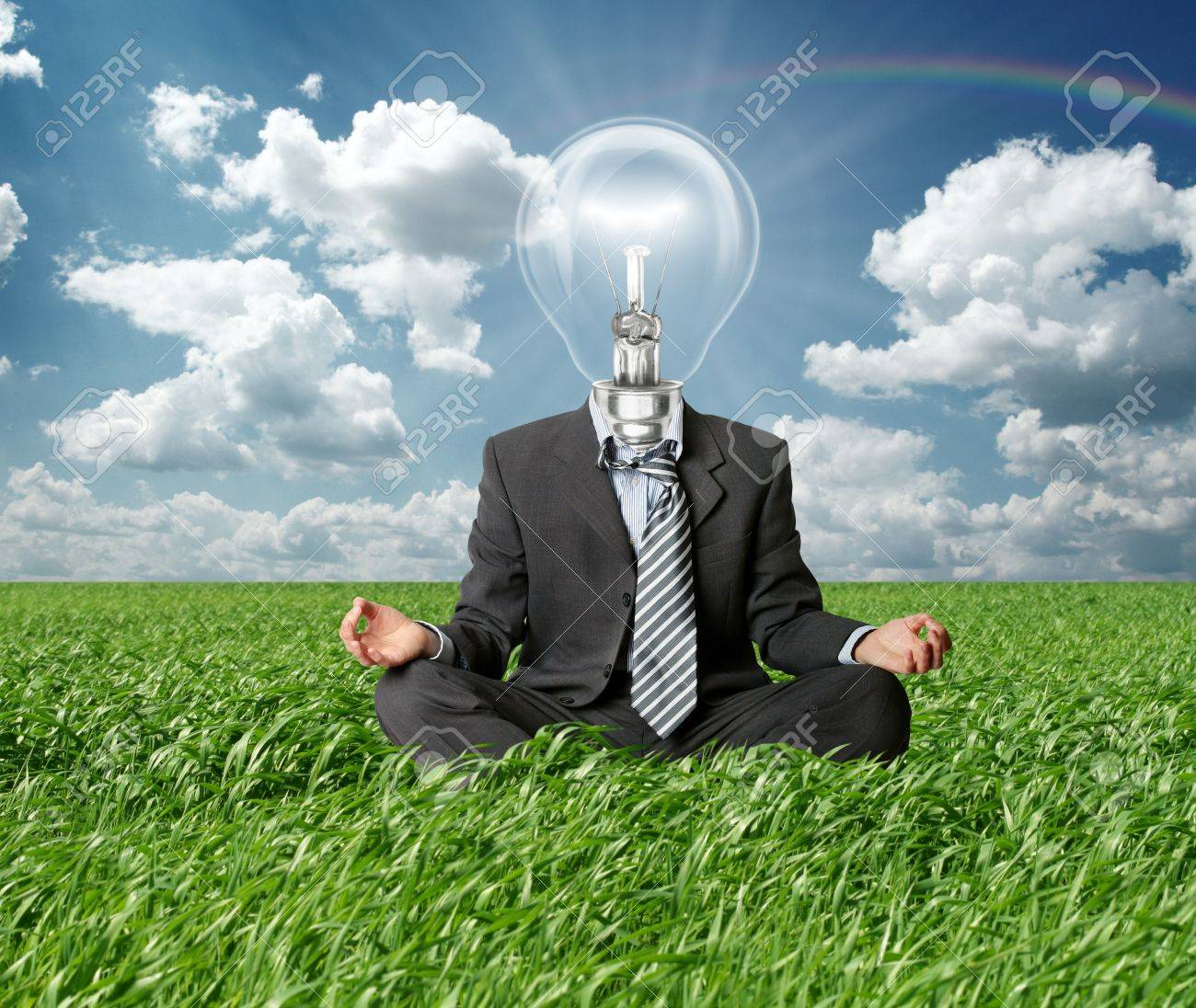 businessman in lotus pose and lamp-head in grass in green grass on blue summer sky Stock Photo - 9621896