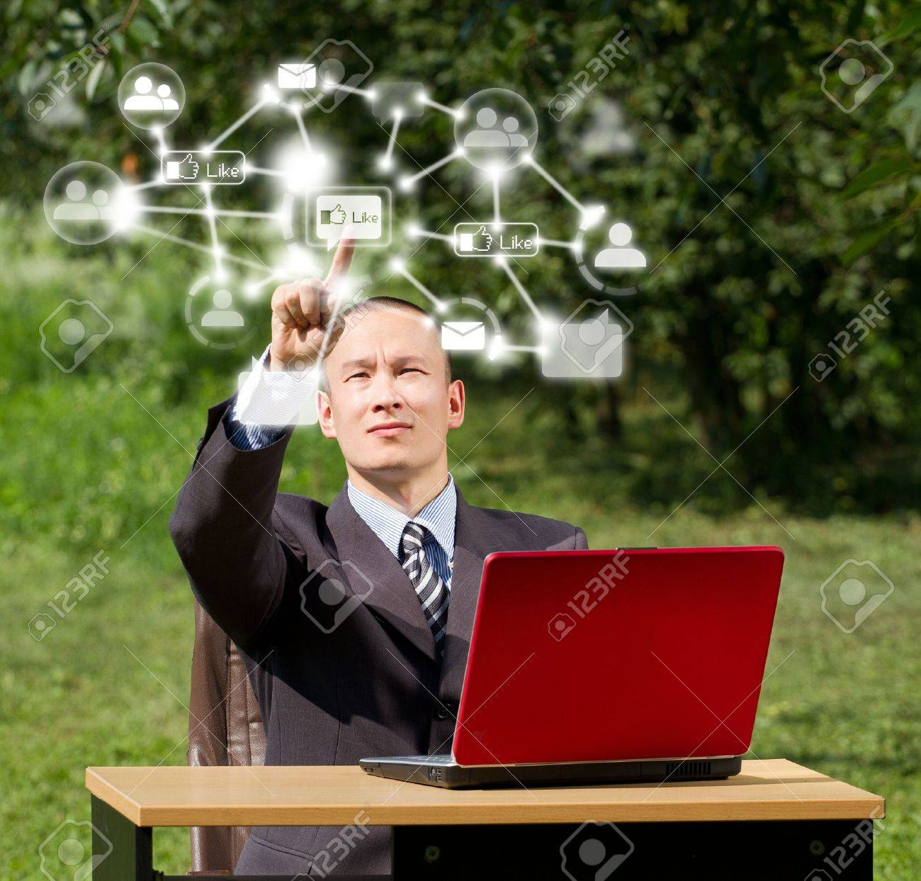 Man with red laptop in social networks outdoors, pushs the button Stock Photo - 12547518