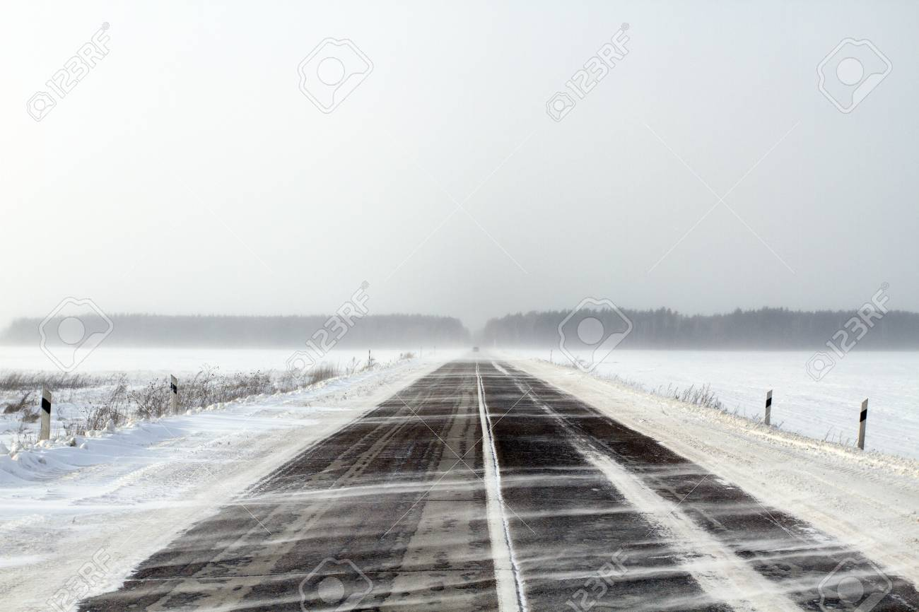 Snowing road in the middle of snow fields Stock Photo - 17239858