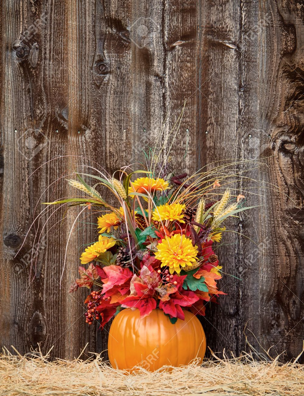 Pumpkin Flower Arrangement On Hay Against Rustic Wooden Background Stock Photo