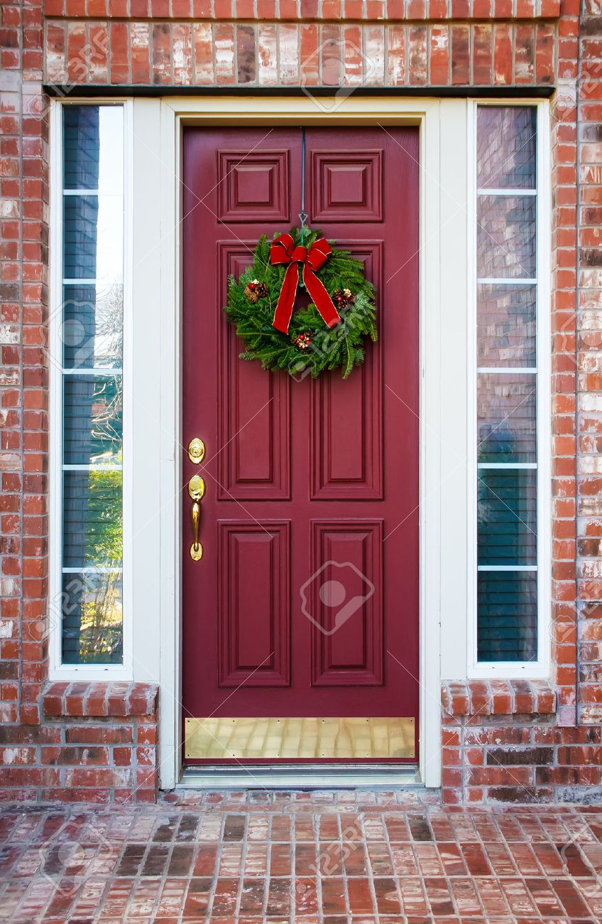 Christmas Wreath Hanging On A Red Wooden Door Of A Brick House Stock Photo    24461238