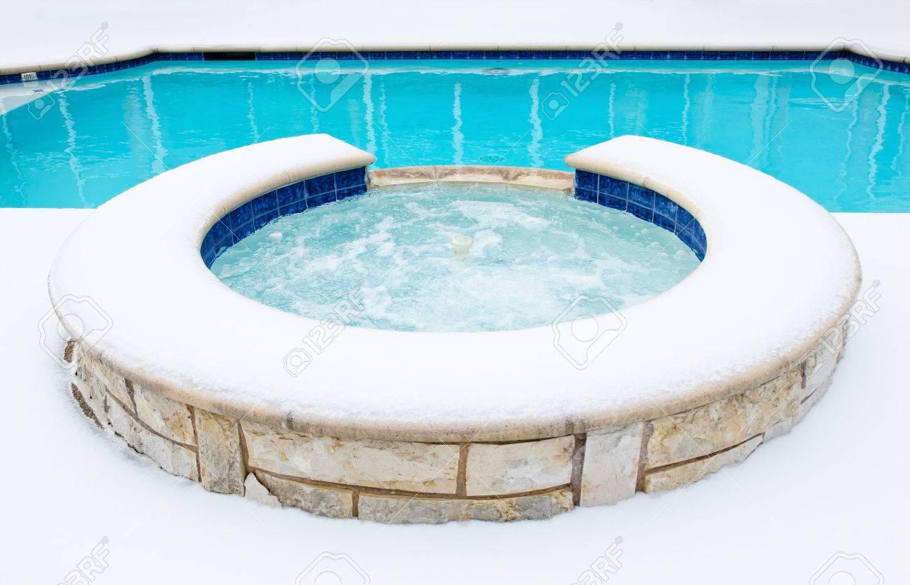 jacuzzi al aire libre residencial o spa por una piscina rodeada por la nieve en el