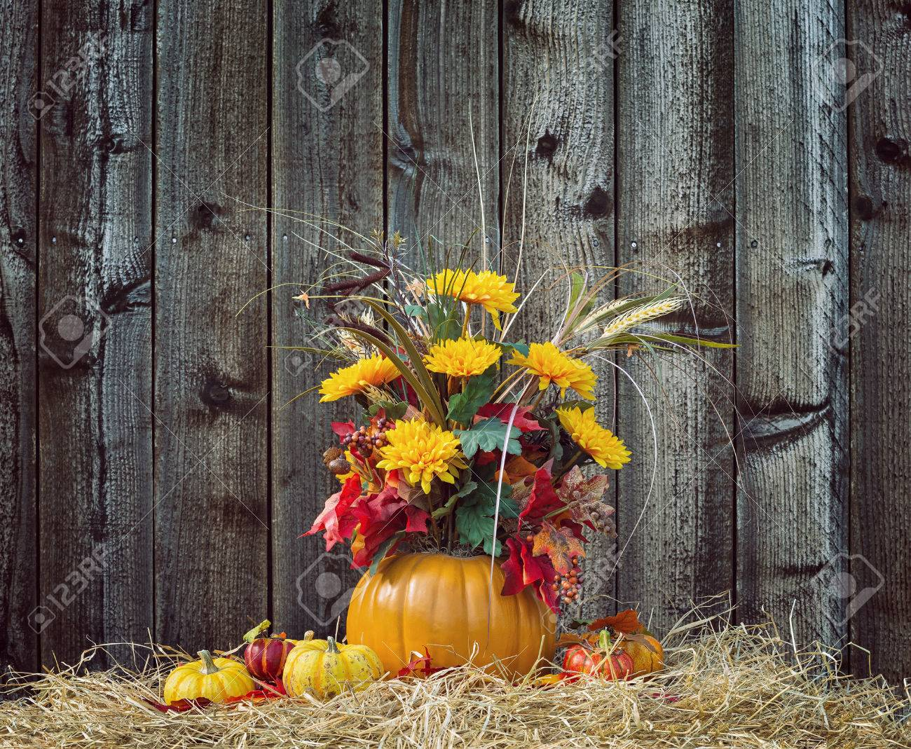 Pumpkin Flower Arrangement Display On Hay Against Rustic Wooden Background Stock Photo