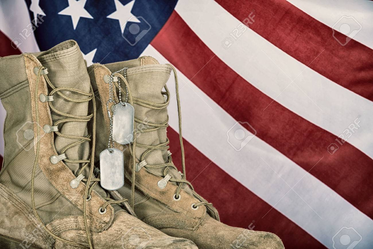 Old combat boots and dog tags with American flag in the background. Vintage filter effects. - 55964912