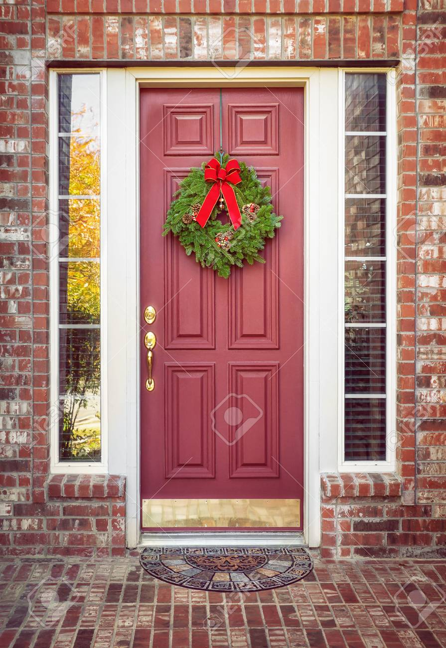 Traditional Balsam Fir Christmas Wreath Hanging On A Red Door