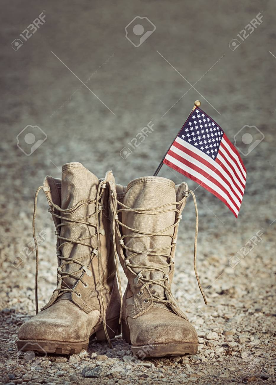 56159c66e9f9 Old military combat boots with the American flag. Rocky gravel background  with copy space.