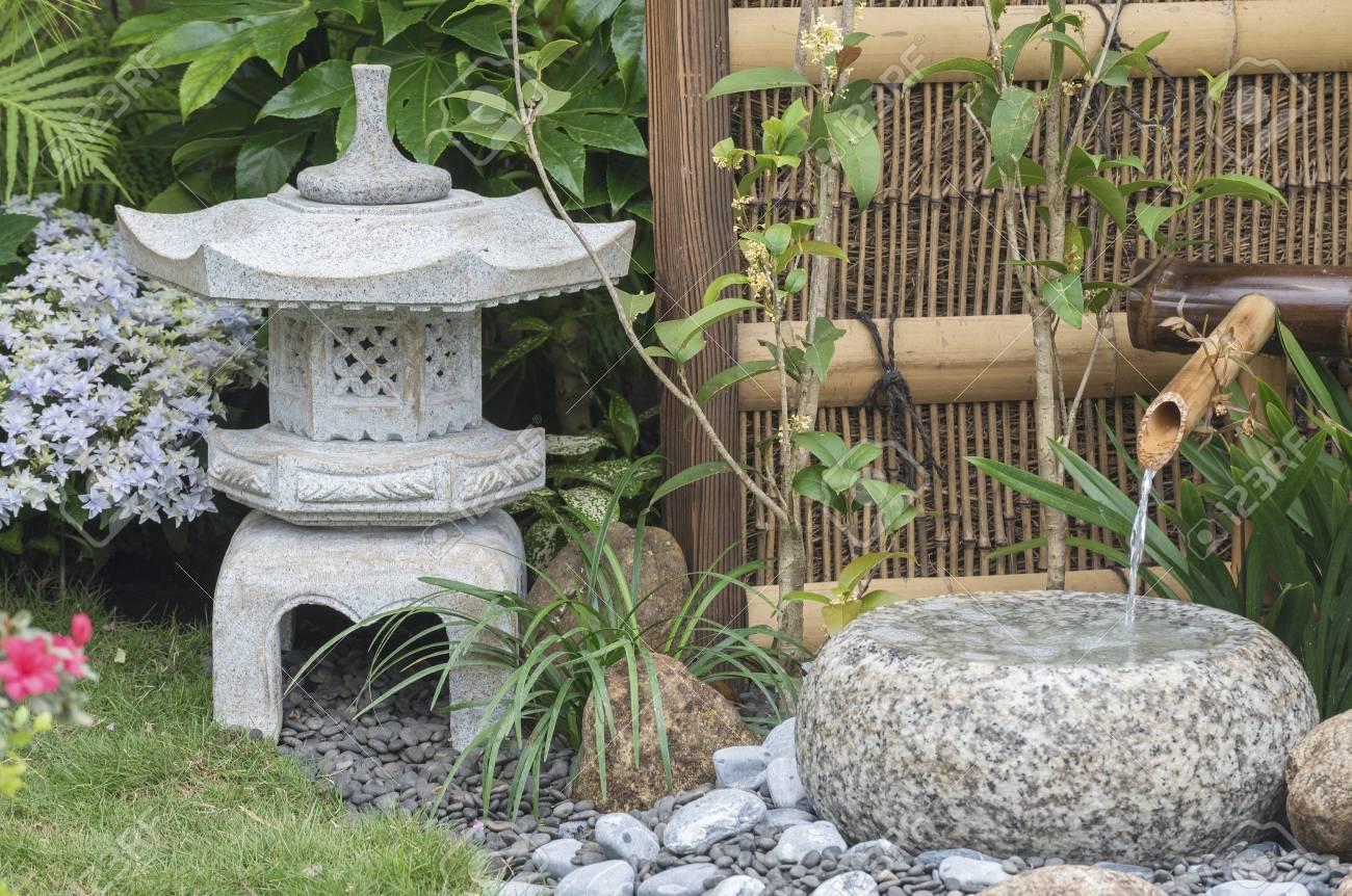 stone lantern and bamboo fountain in Japanese garden - 75162376