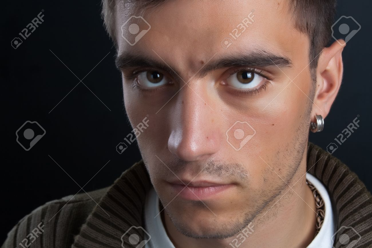 Portrait Of Beautiful And Attractive Young Man With Penetrating Eyes And A  Silver Earring In Closeup