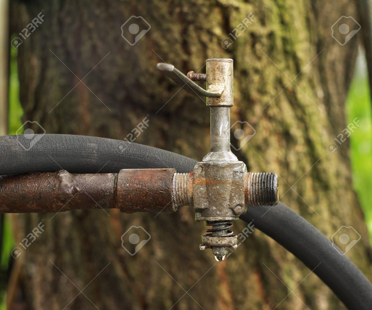 ein alter wasserhahn auf einem rostigen rohr und schlauch für die