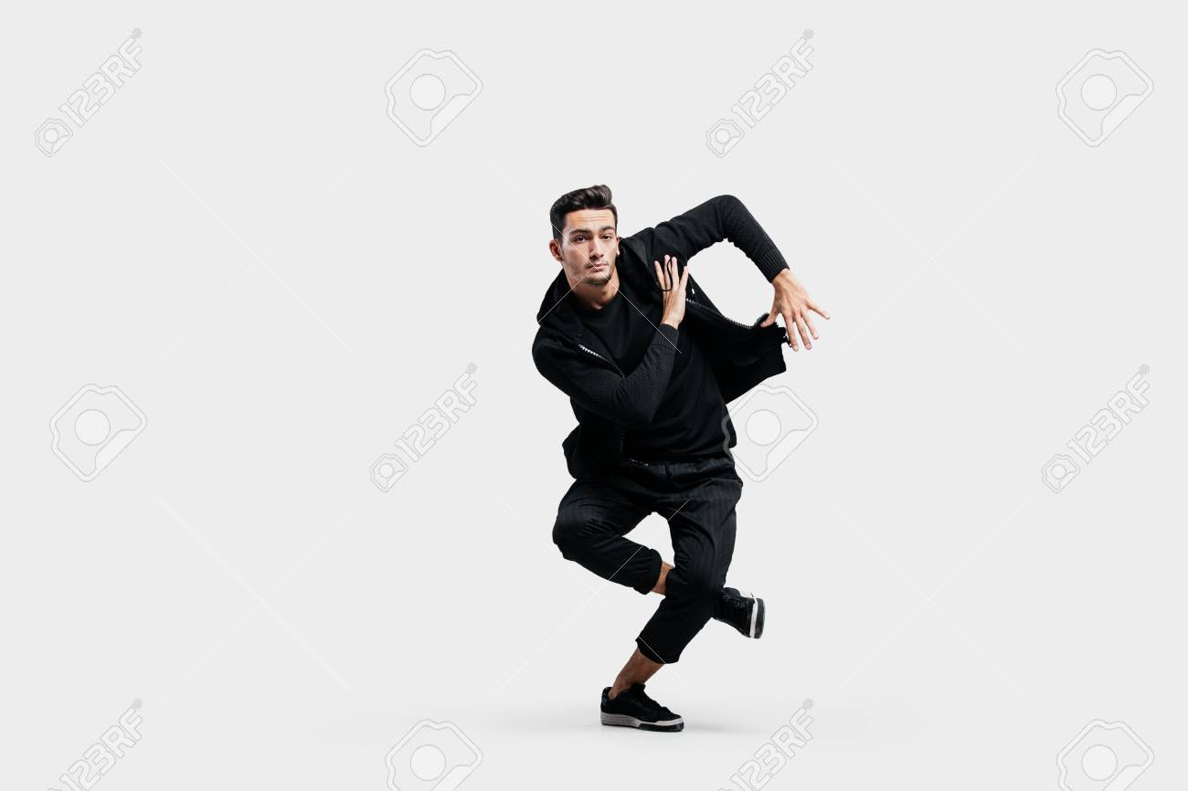 064e1287 Stock Photo - Stylish young man wearing a black sweatshirt and black pants  makes stylized movements of hip-poh