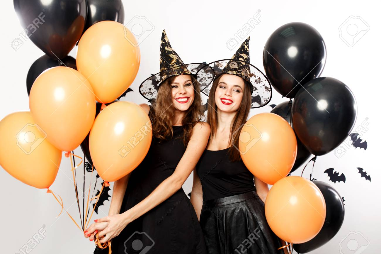 Two beautiful women in black dresses and witch`s hats have fun with black and orange balloons. Halloween party - 111421340