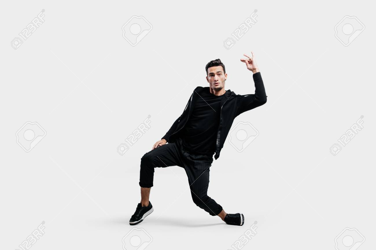 de4ee1e0 Stock Photo - Stylish young dancer wearing a black sweatshirt and black  pants makes stylized movements of hip-poh