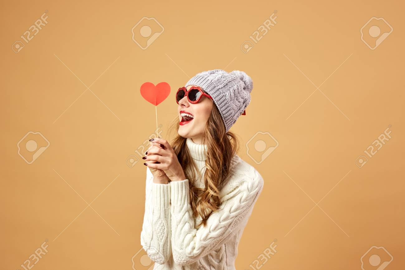 9bc026acbaa Happy girl in sunglasses dressed in white knitted sweater and hat haves fun  with a red